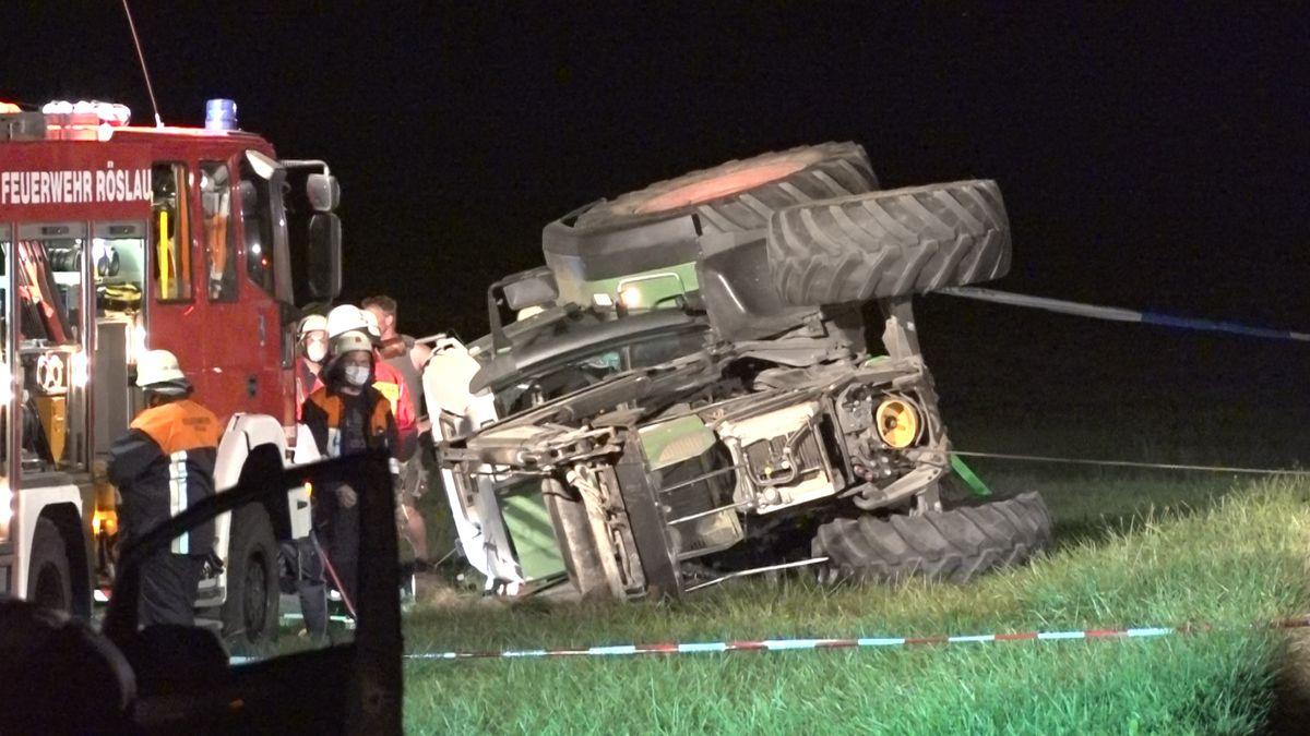 Feuerwehrleute stehen neben dem seitlich umgekippten Traktor, der umgestürzt war.