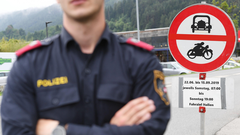 Österreich, Kematen: Ein Polizist steht vor einem Schild, das auf die Sperrung für den Verkehr mit Fahrziel Italien hinweist.