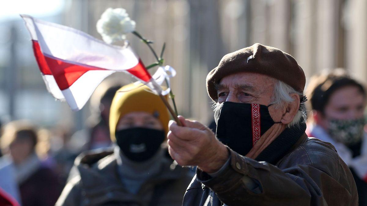Ein Demonstrant mit einer belarussischen Fahne und einer Blume in der Hand