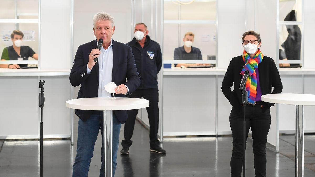 Münchens OB Dieter Reiter und Gesundheitsreferentin Beatrix Zurek vor den Check-in-Schaltern im Impfzentrum.