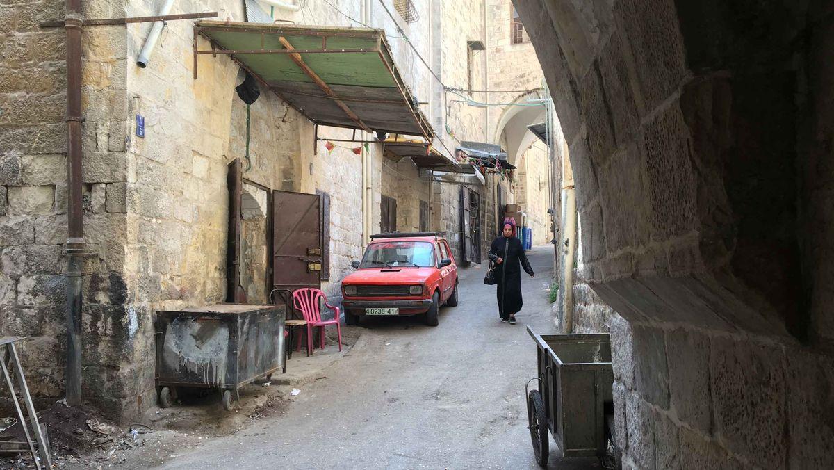 Eine palästinensische Frau mit Kopftuch geht durch die engen Gassen der Nabluser Altstadt.
