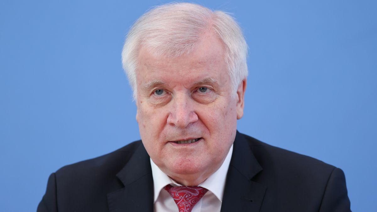 Portrait-Aufnahme Horst Seehofer, schwarzes Jacket, weißes Hemd und rot-gemusterte Krawatte, blauer Hintergrund
