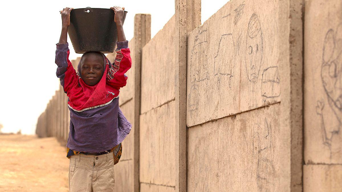 Ein Bub arbeitet auf einer Baustelle in Afrika.