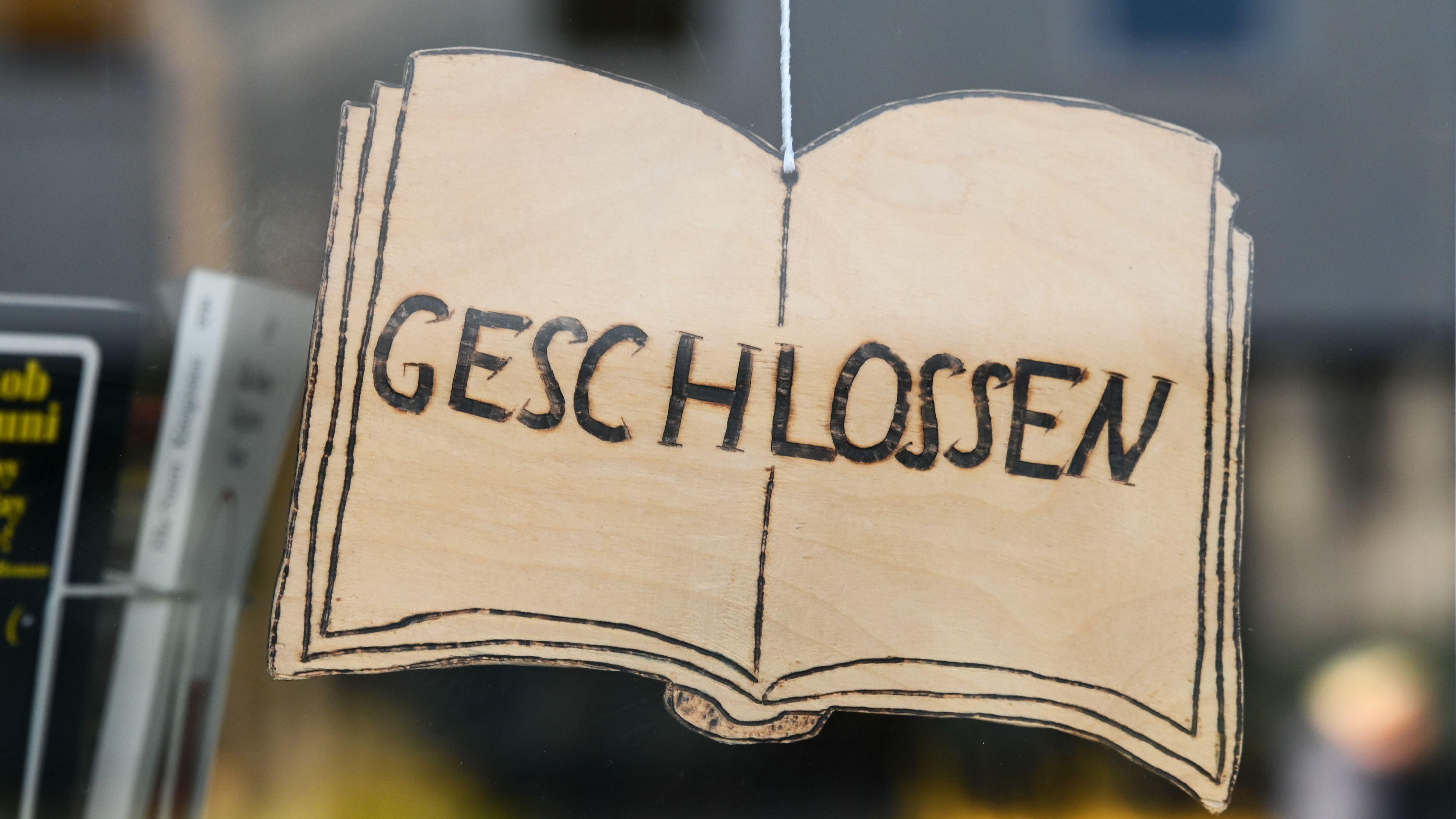 """""""Geschlossen"""" steht auf dem Schild einer Buchhandlung in Kassel, gestaltet wie ein Buch. Buchhändlerinnen und Buchhändler in Deutschland – und mit ihnen die Verlage – stehen vor gewaltigen Herausforderungen."""