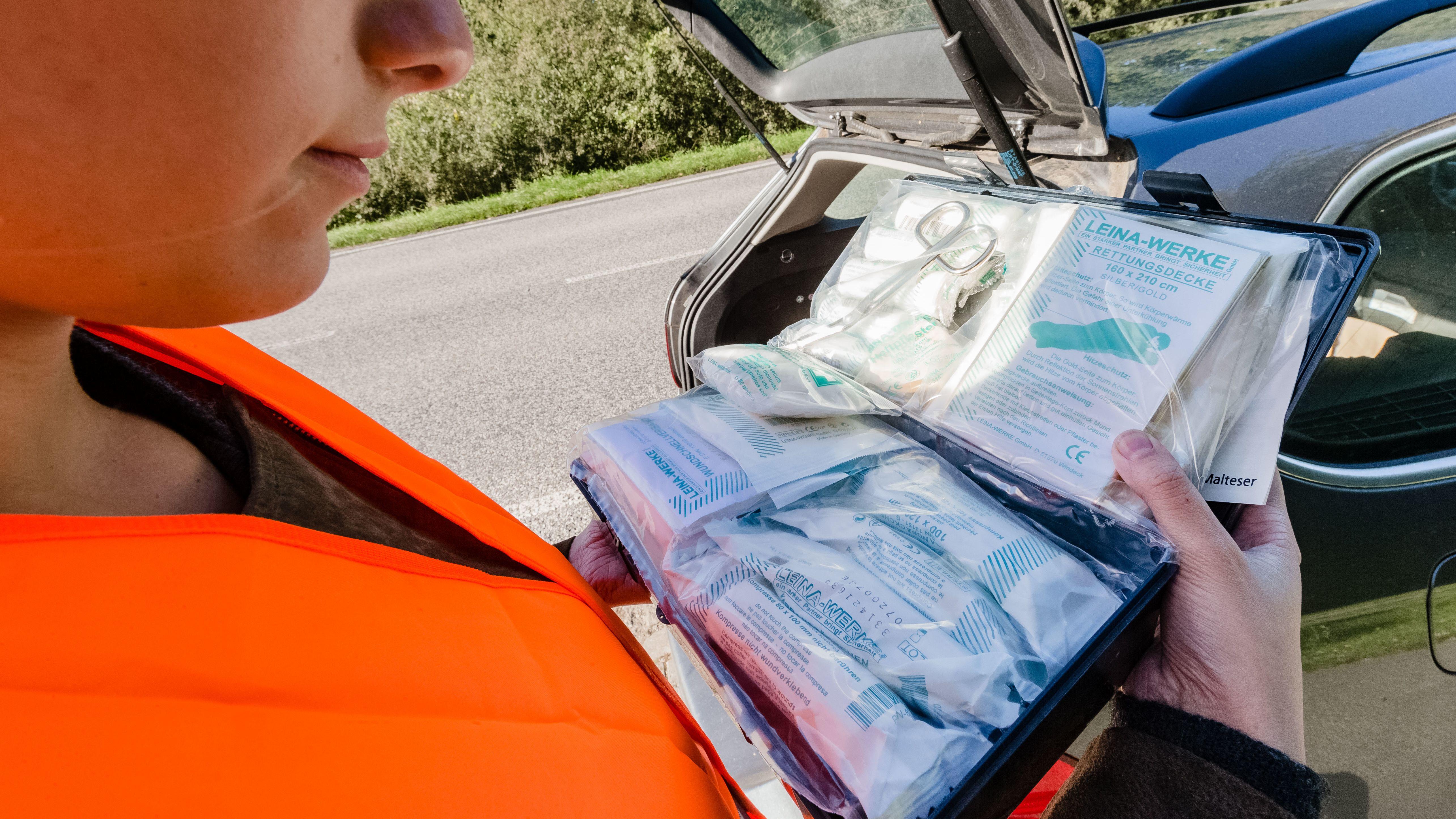 Frau mit Verbandskasten im Auto