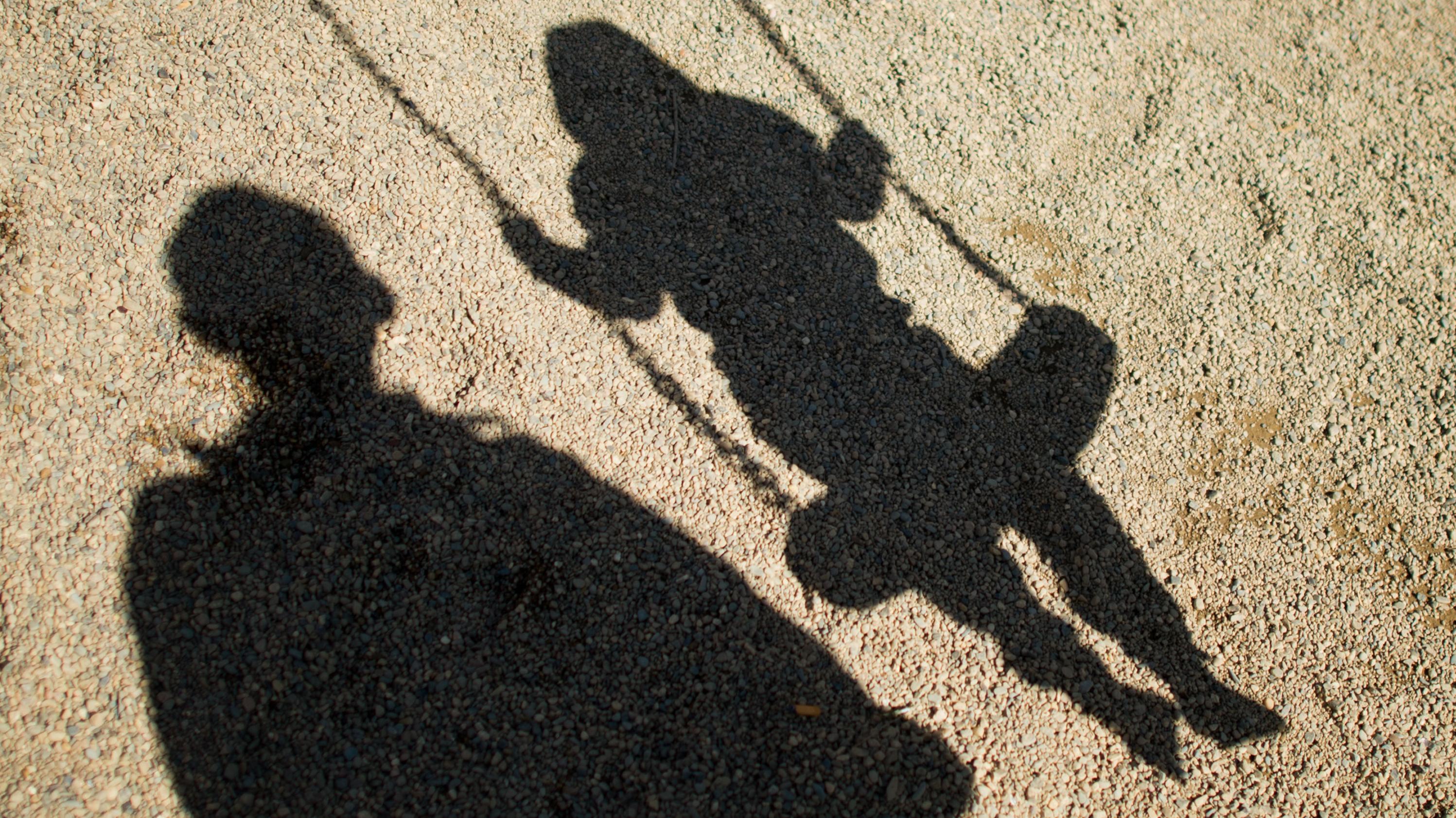 Der Schatten von einem Mann und einem schaukelnden Kind