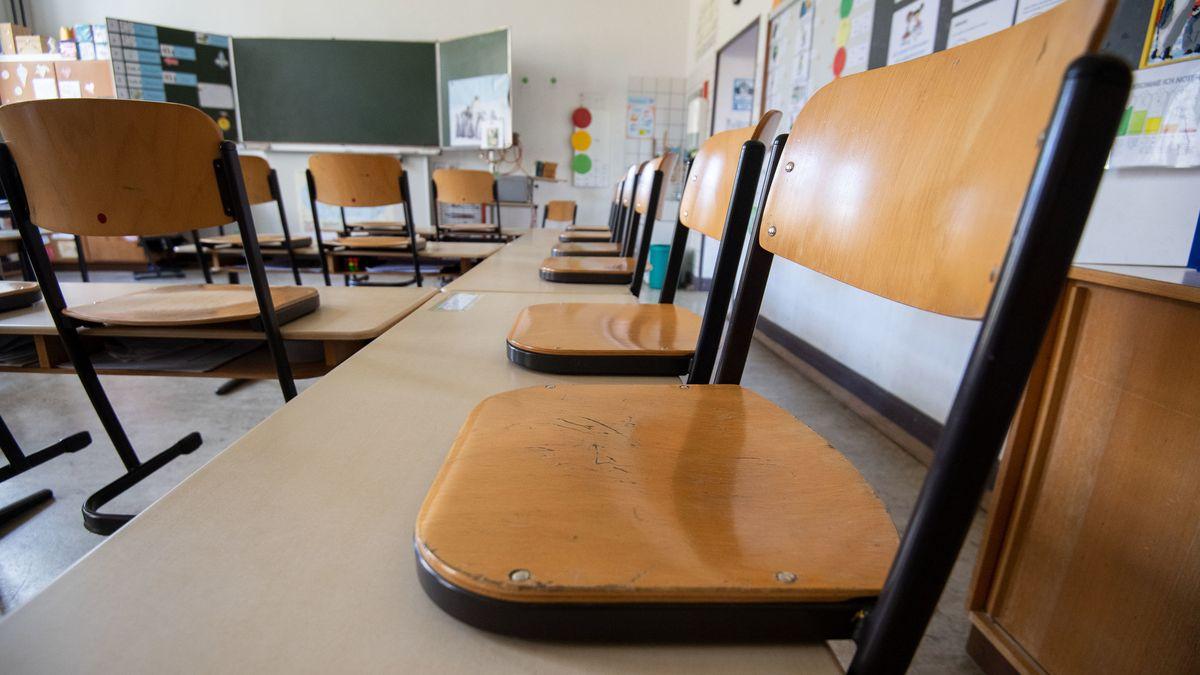 Stühle stehen in einem leeren Klassenzimmer auf den Tischen.