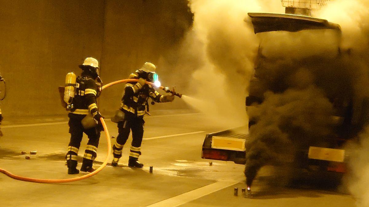 Zwei Feuerwehrleute mit einem Löschschlauch, rechts ein qualmender LKW