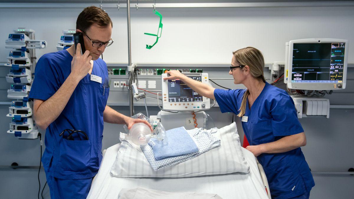 Zwei Krankenhausmitarbeiter richten ein Bett her.