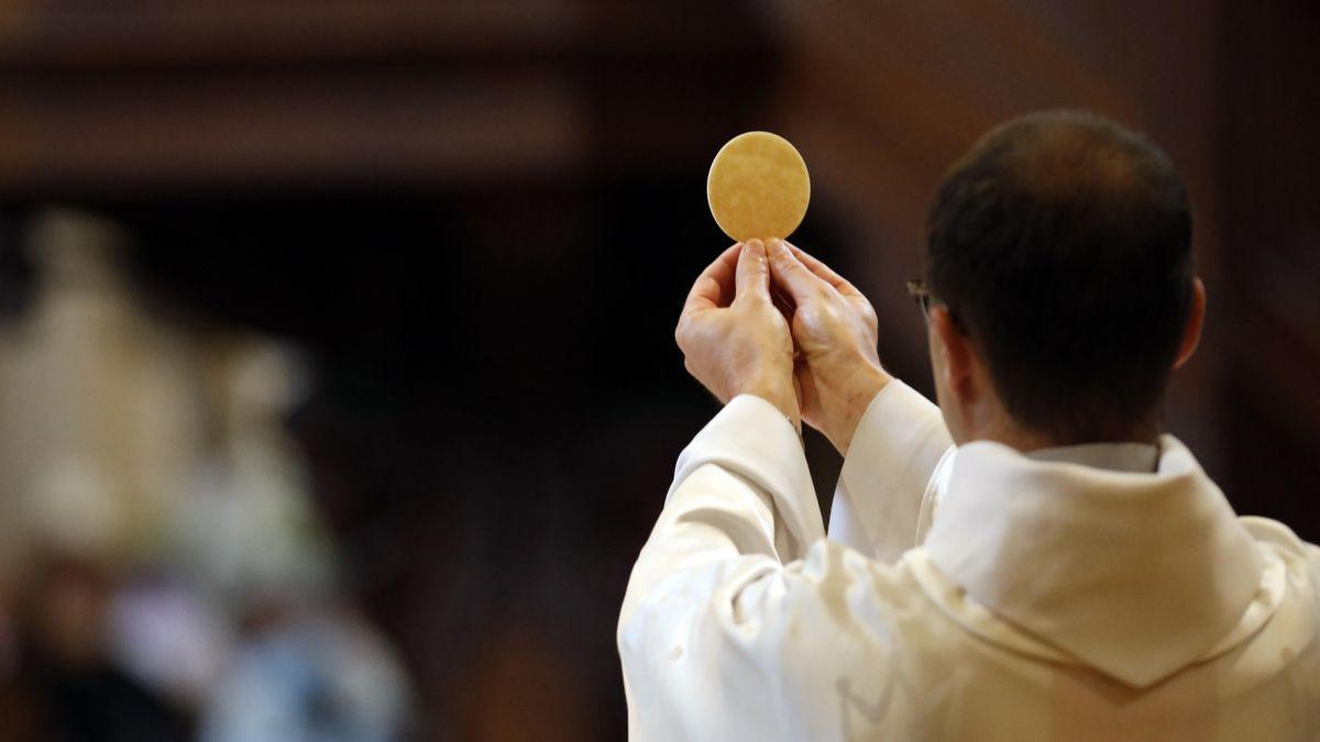 Eucharistie-Feier in einer katholischen Kirche: Pfarrer hält eine Hostie mit beiden Händen hoch.