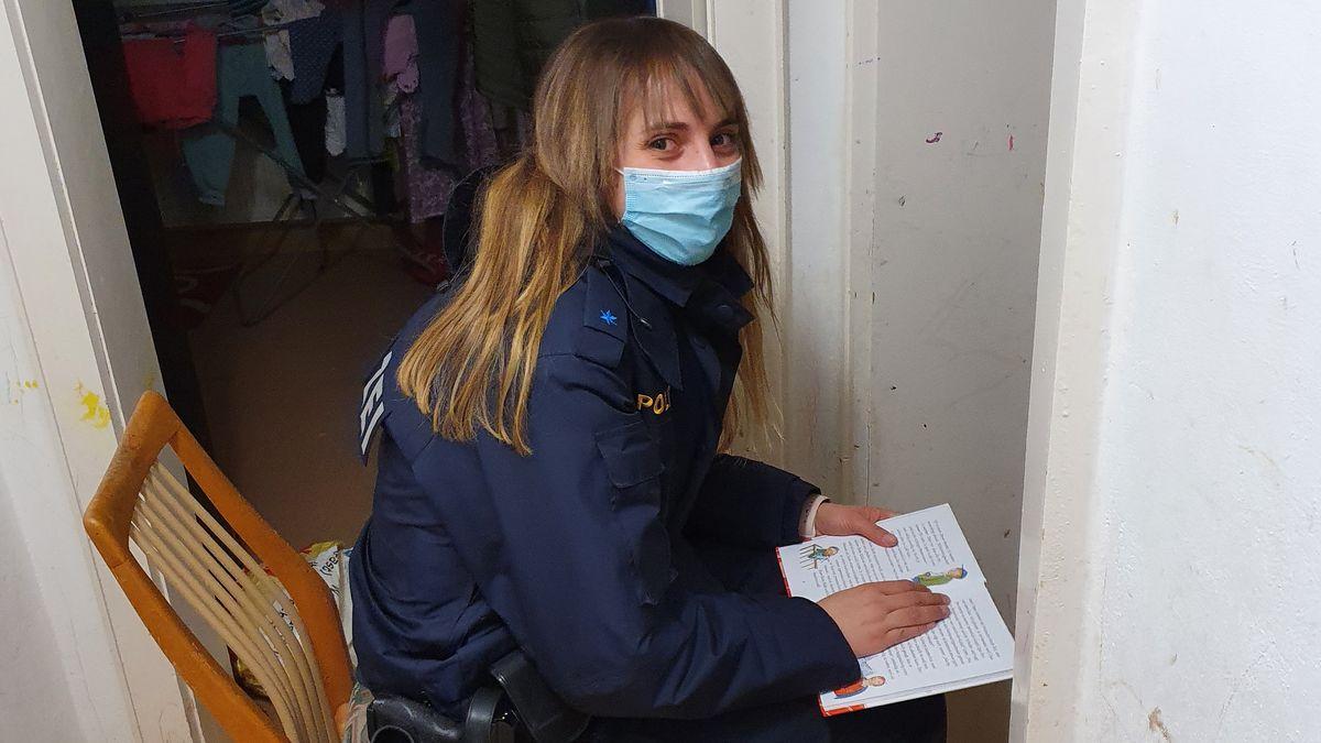 Eine junge Polizistin liest aus einem Buch vor.