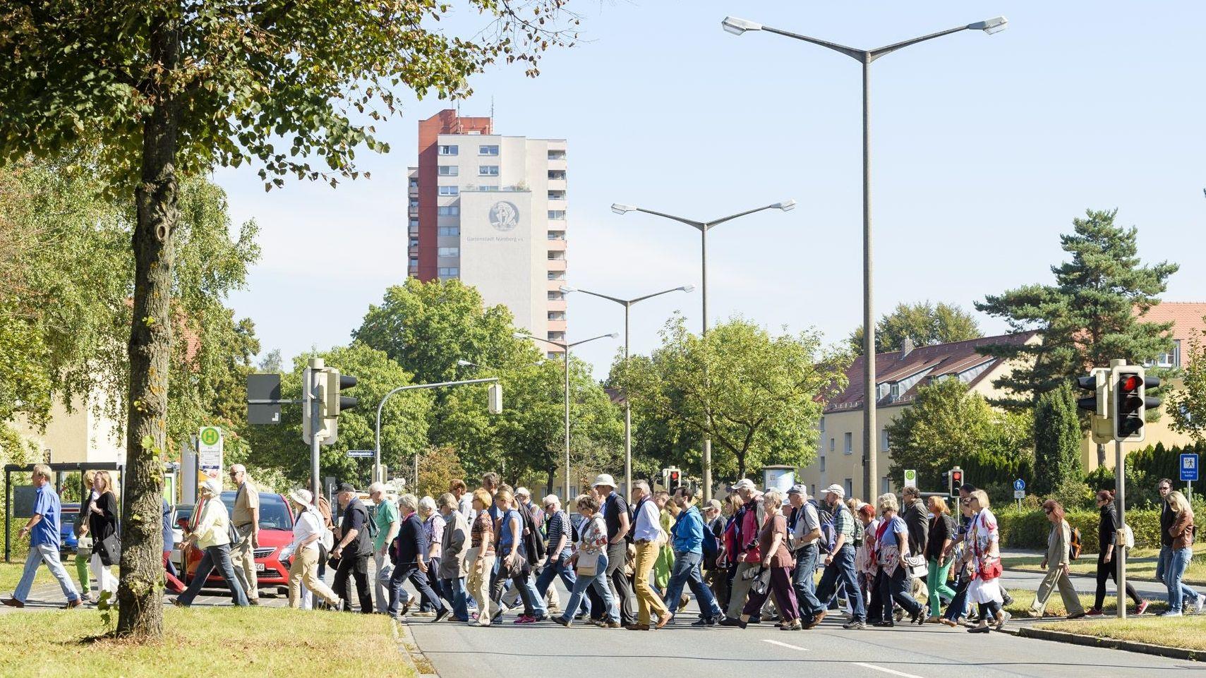 Eine Gruppe von Menschen kreuzt die Straße bei der Stadtverführung in der Nürnberger Gartenstadt