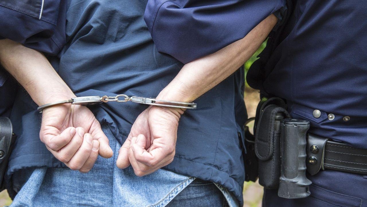 Ein Mann in Handschellen, daneben ein Polizist (Symbolbild)
