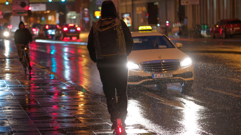 Ein E-Scooter fährt bei Regenwetter durch die Innenstadt. Vor Beginn der kalten Jahreszeit hat der TÜV-Verband die Anbieter von E-Tretrollern aufgefordert, ihre Mietangebote bei schlechtem Wetter zu sperren.