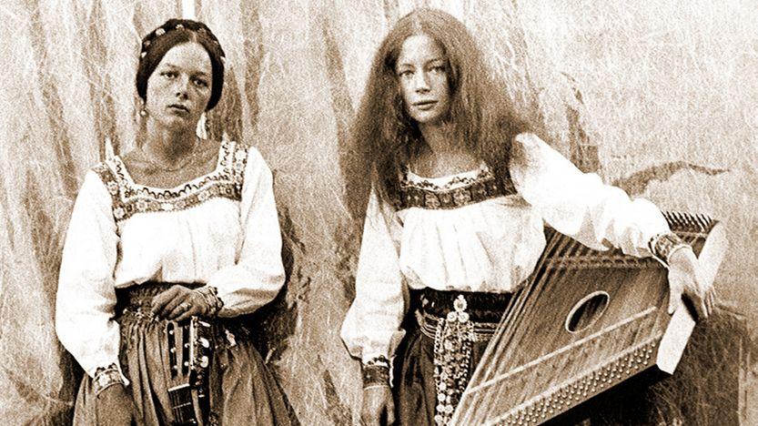 """Filmbild aus """"Walchensee Forever"""": Die Schwestern Frauke und Anna Werner in Hippieblusen mit Hackbrett und Gitarre vor einem Heuhafen (Schwarzweiß-Aufnahme)"""