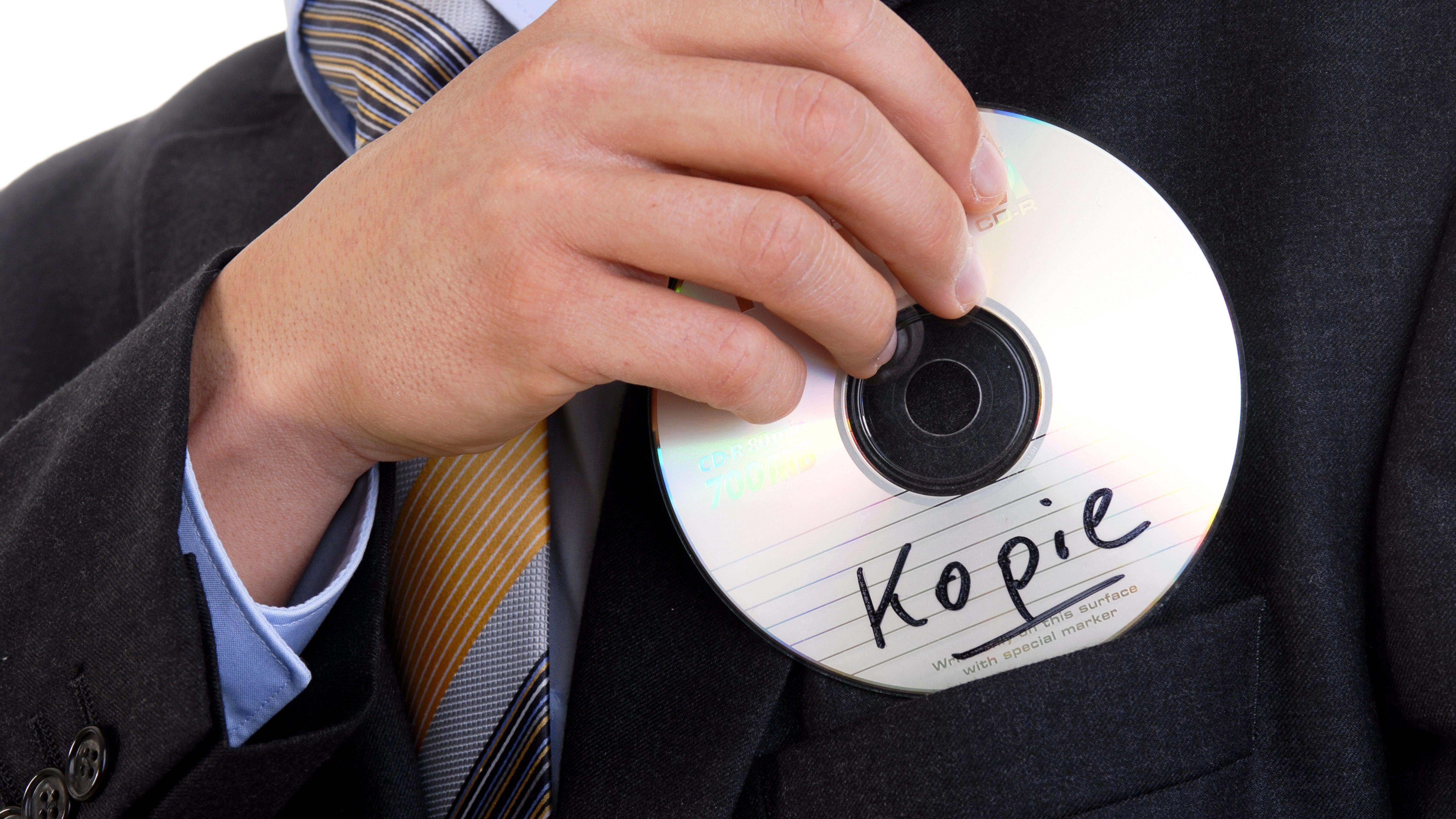 """Mann steckt CD mit Aufschrift """"Kopie"""" ein"""