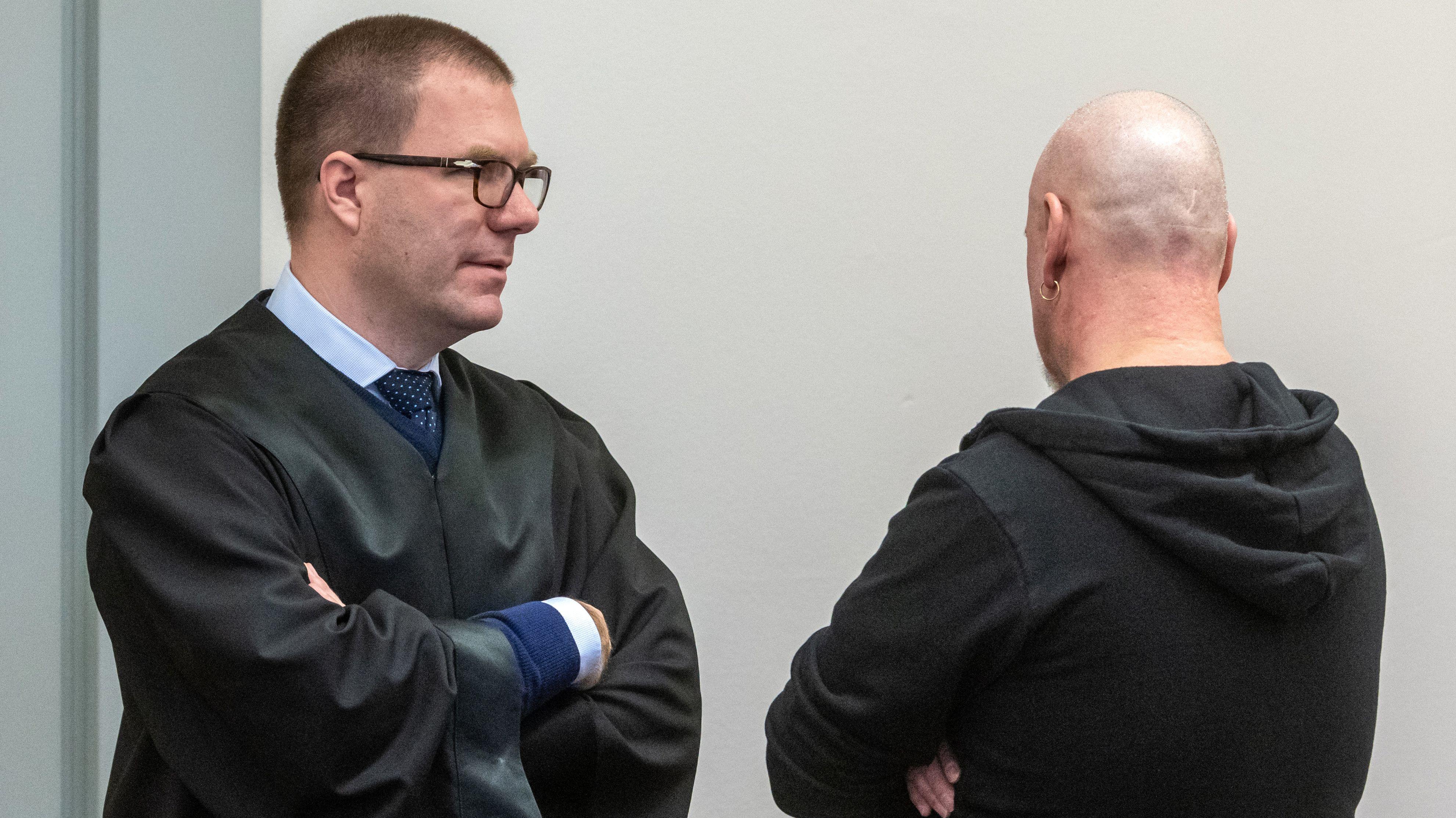 Der Angeklagte (re.) steht im Verhandlungssaal des Landgerichts neben seinem Verteidiger Sebastian Gaßmann.