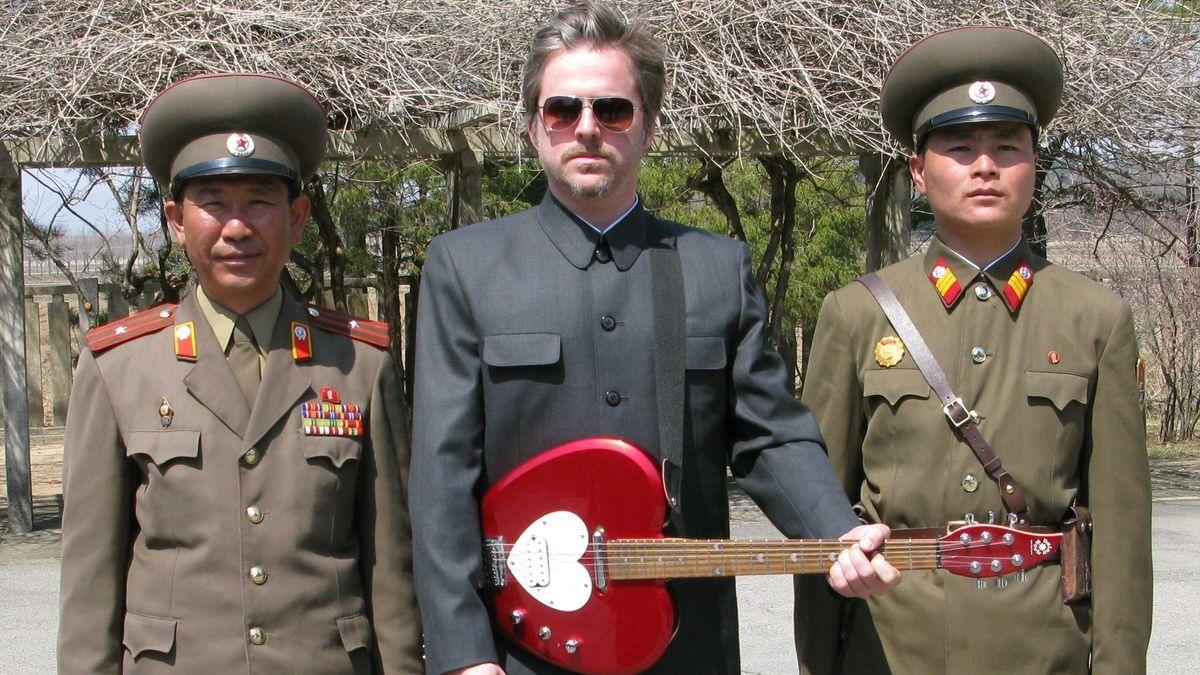 Morten Traavis mit roter E-Gitarre zwischen zwei nordkoreanischen Uniformierten