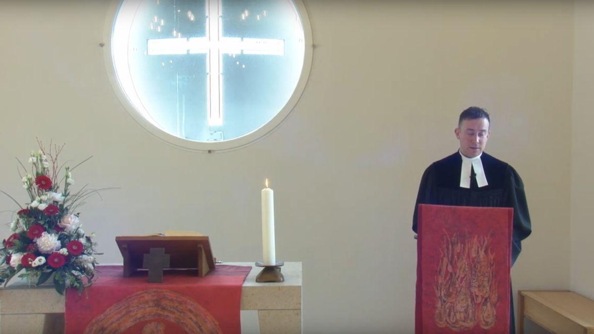 Ein Pfarrer steht vor einem Rednerpult in der Kirche
