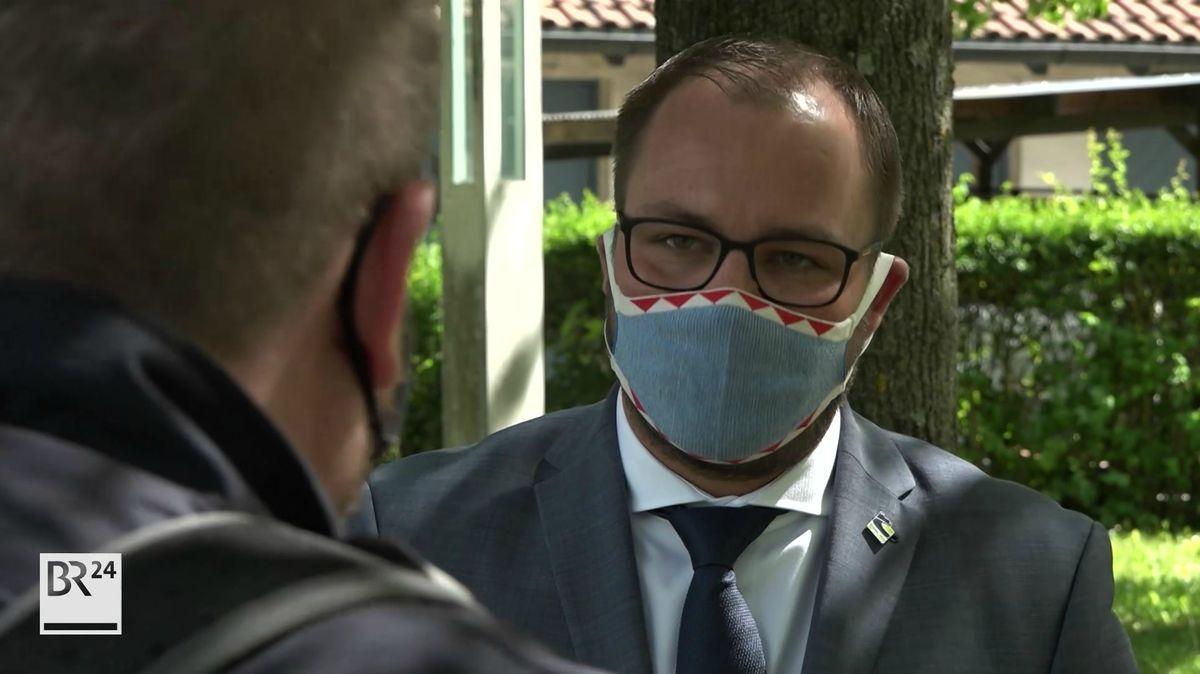 Coburgs Landrat Sebastian Straubel (CSU) mit Mundschutz im Gespräch mit BR-Reporter Richard Krill.