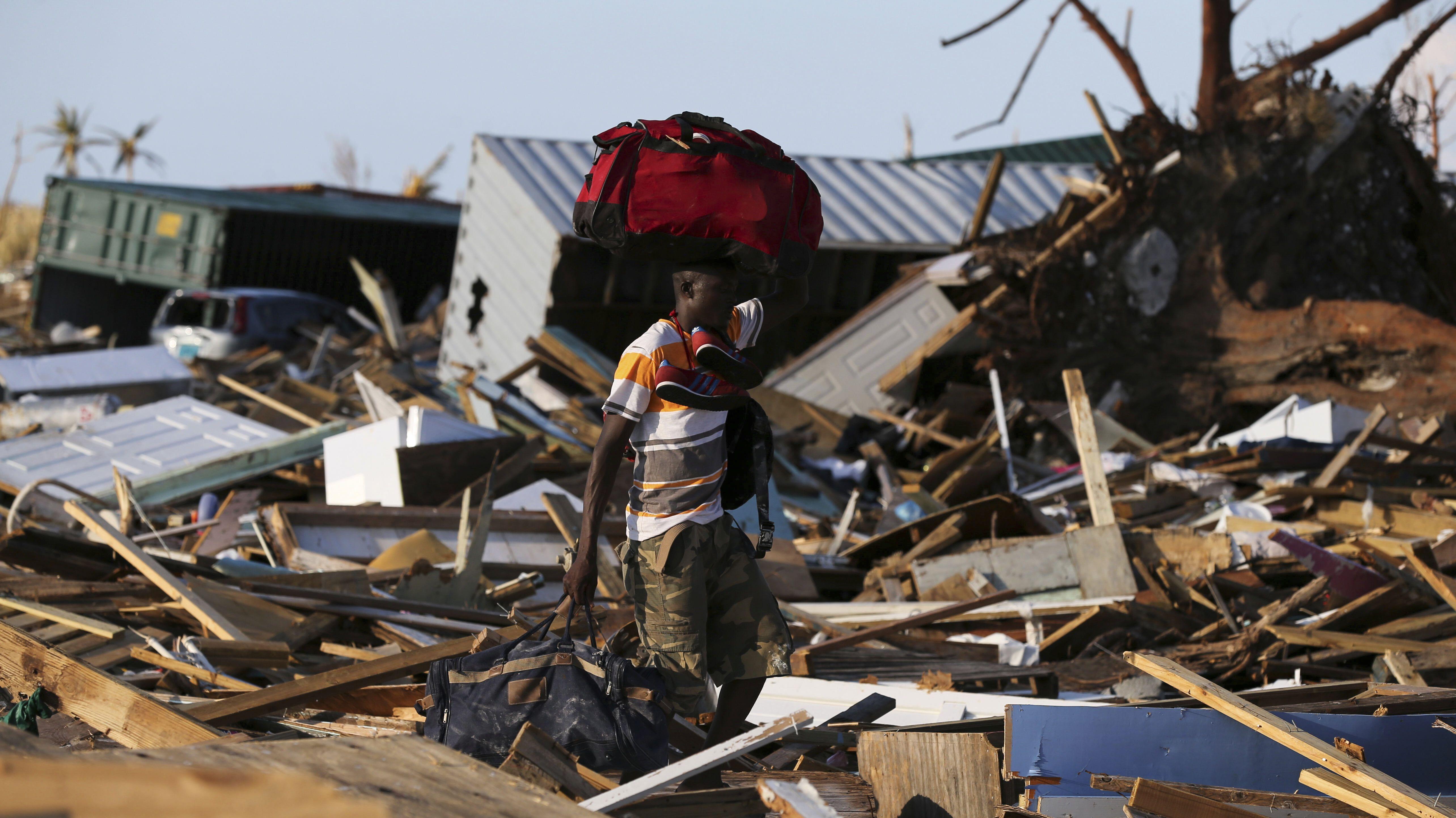 """Ein Mann trägt seine Habseligkeiten auf dem Rücken, während er durch das vom Hurrikan """"Dorian"""" zerstörte Wohngebiet läuft."""