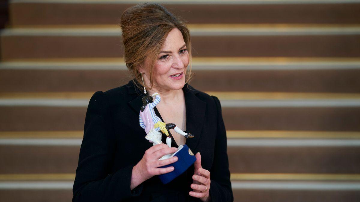 Man sieht die prämierte Schauspielerin Martina Gedeck mit dem Bayerischen Filmpreis in Gestalt der Porzellanfigur Pierrot