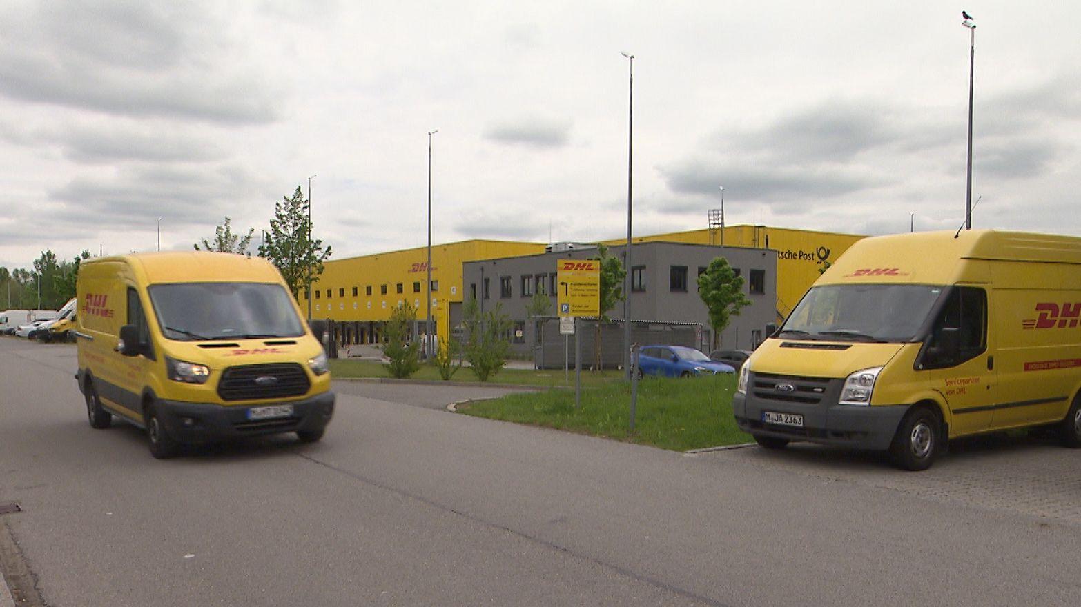 Fahrzeuge songenannter Servicepartner von DHL vor einem Logistikzentrum