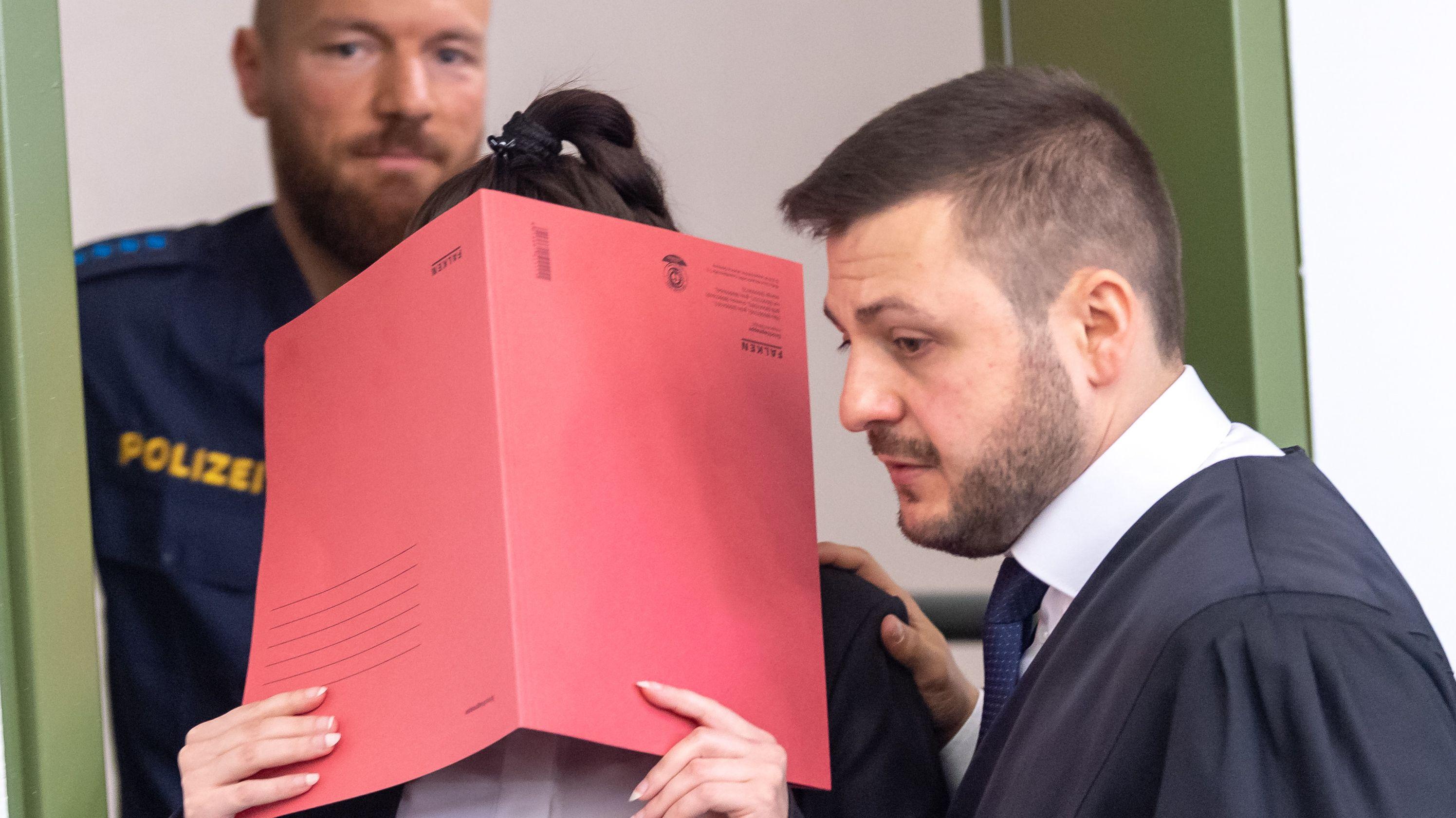 Die Angeklagte Jennifer W. halt sich beim Betreten des Gerichtssaals in München einen Aktendeckel vor das Gesicht. (Archivbild vom 9. April 2019)