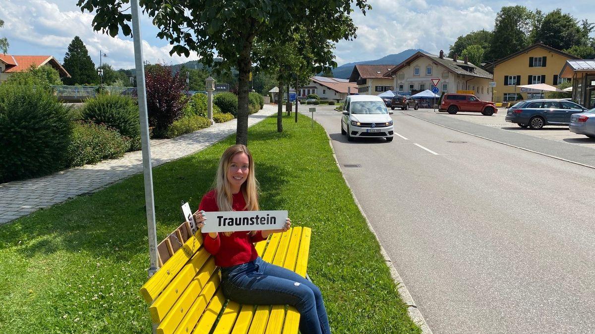 """Eine Frau sitzt auf einer gelben Bank und hält ein Schild mit der Aufschrift """"Traunstein"""" hoch."""