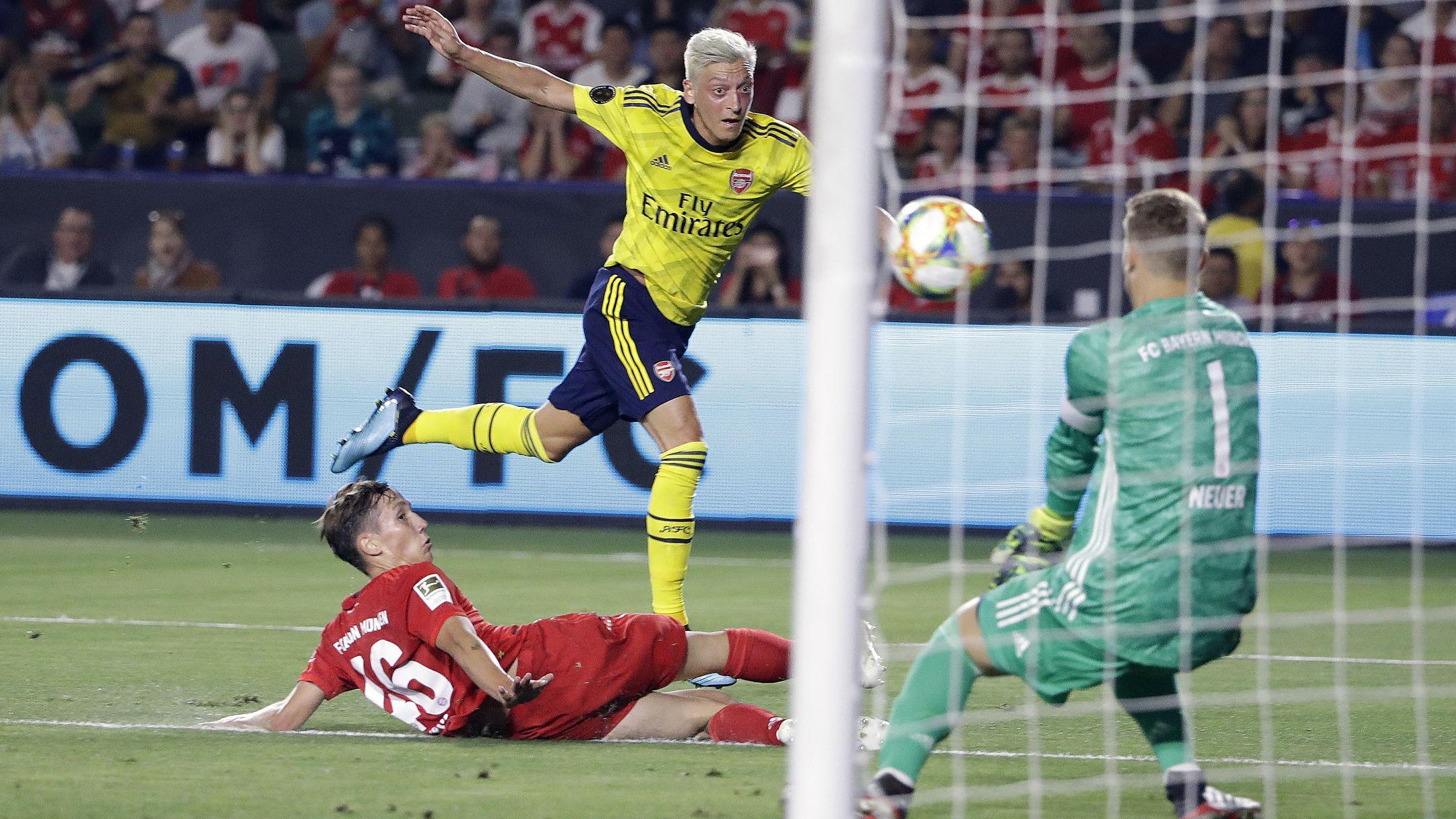 Jonas Kehl (l) und Torhüter ManuelNeuer (r) gegen Arsenals Mesut Özil.