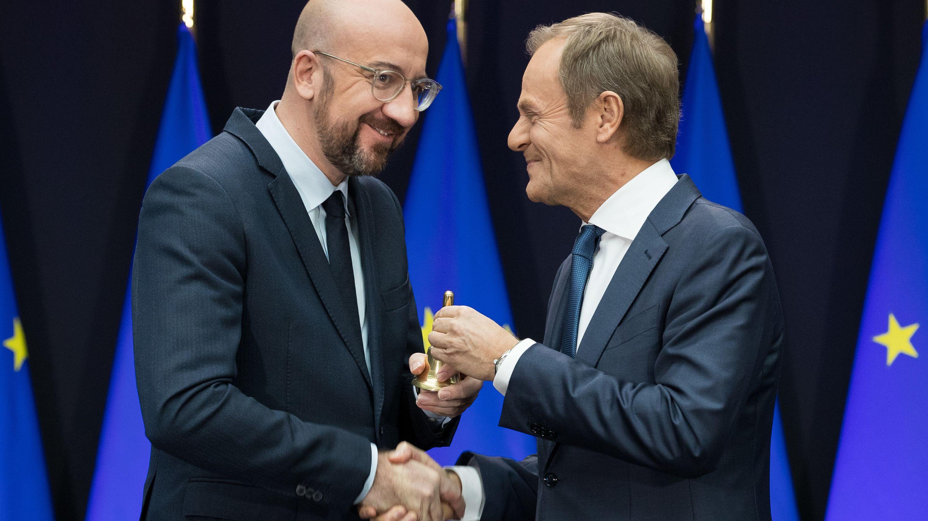Charles Michel (l), neuer Präsident des Europäischen Rates, und Donald Tusk, scheidender Präsident des Europäischen Rates, reichen sich während des symbolischen Akts der Amtsübergabe die Hand, mit der anderen wird die Glocke überreicht.
