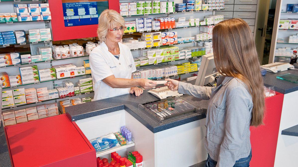 Eine Frau überreicht einer Apothekerin ein Rezept.
