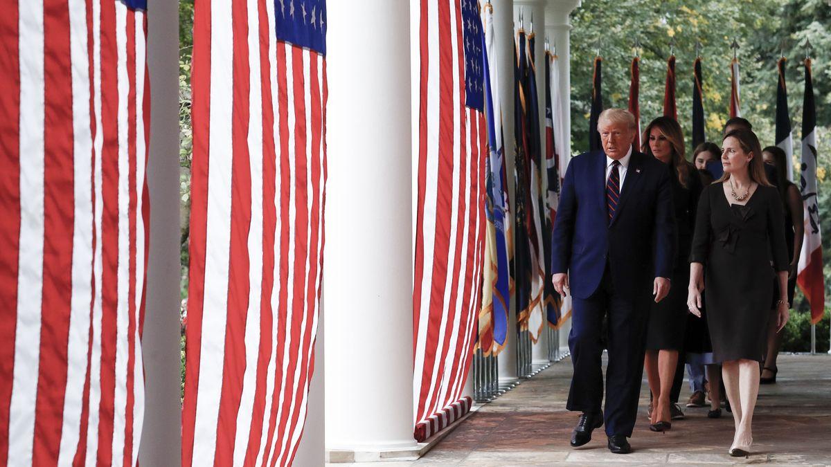 Donald Trump läuft mit Amy Coney Barrett im Rose Garden des White House, im Vordergrund Flaggen der USA.
