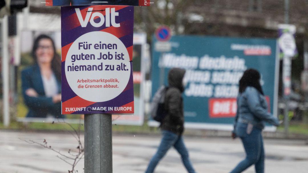 Ein Wahlplakat der Partei Volt hängt vor Großplakaten an einem Laternenmast.