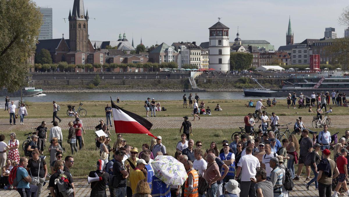 Eine Demo gegen Corona-Regeln auf den Rheinwiesen in Düsseldorf steht ein Mann mit Reichskriegsflagge umringt von Menschen.