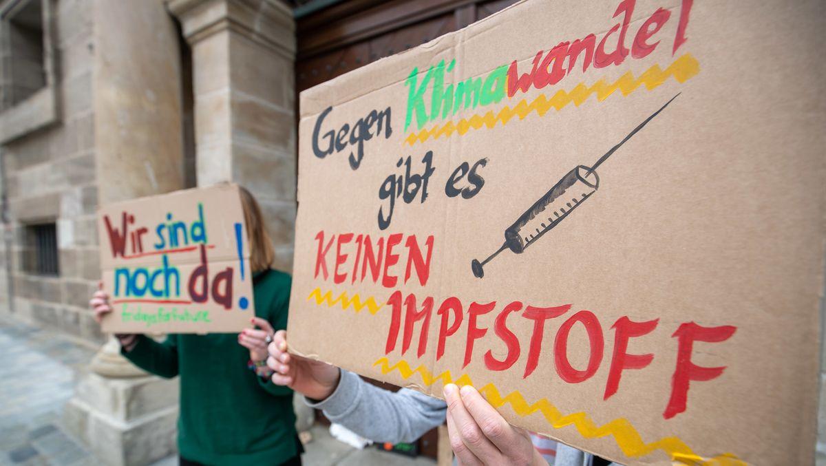 """Klimaprotest in Nürnberg: Zwei Mädchen halten selbstgemachte Plakate, hoch auf denen steht: """"Wir sind noch da"""" und """"Gegen Klimawandel gibt es keinen Impfstoff"""""""