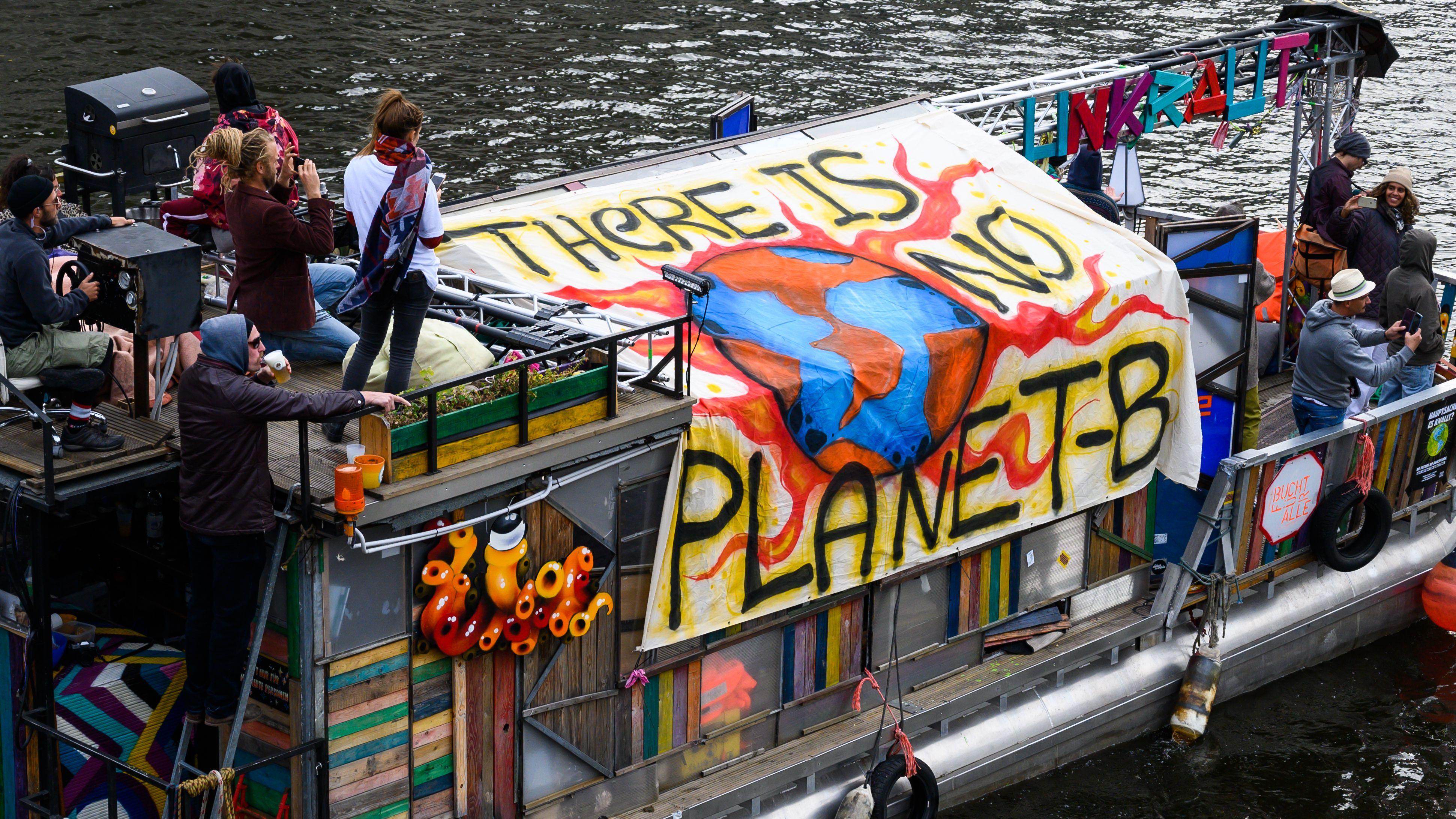 """Ein Boot eines Bootskorsos mit dem Motto """"There's no Planet B"""", fährt auf der Spree am Reichstag vorbei."""