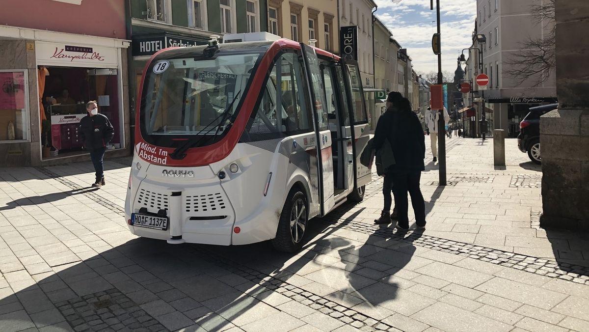 Passagiere steigen in Hof in einen selbstfahrenden Bus ein.