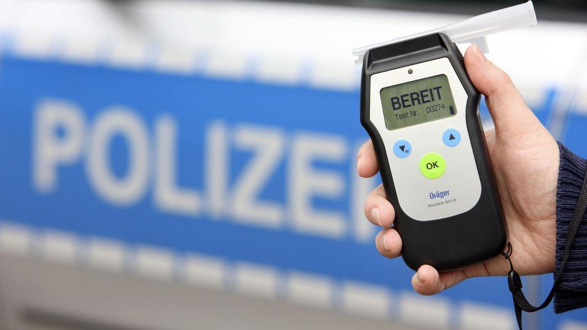 Eine Hand hält eine Alkohol-Messgerät, im Hintergrund ein Polizeiauto.