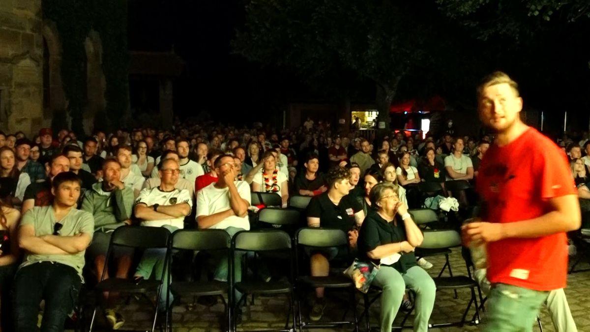 Zuaschauer sitzen auf Stühlen uns schauen das erste Spiel der deutschen Nationalmannschaft bei der Fußball-Europameisterschaft.