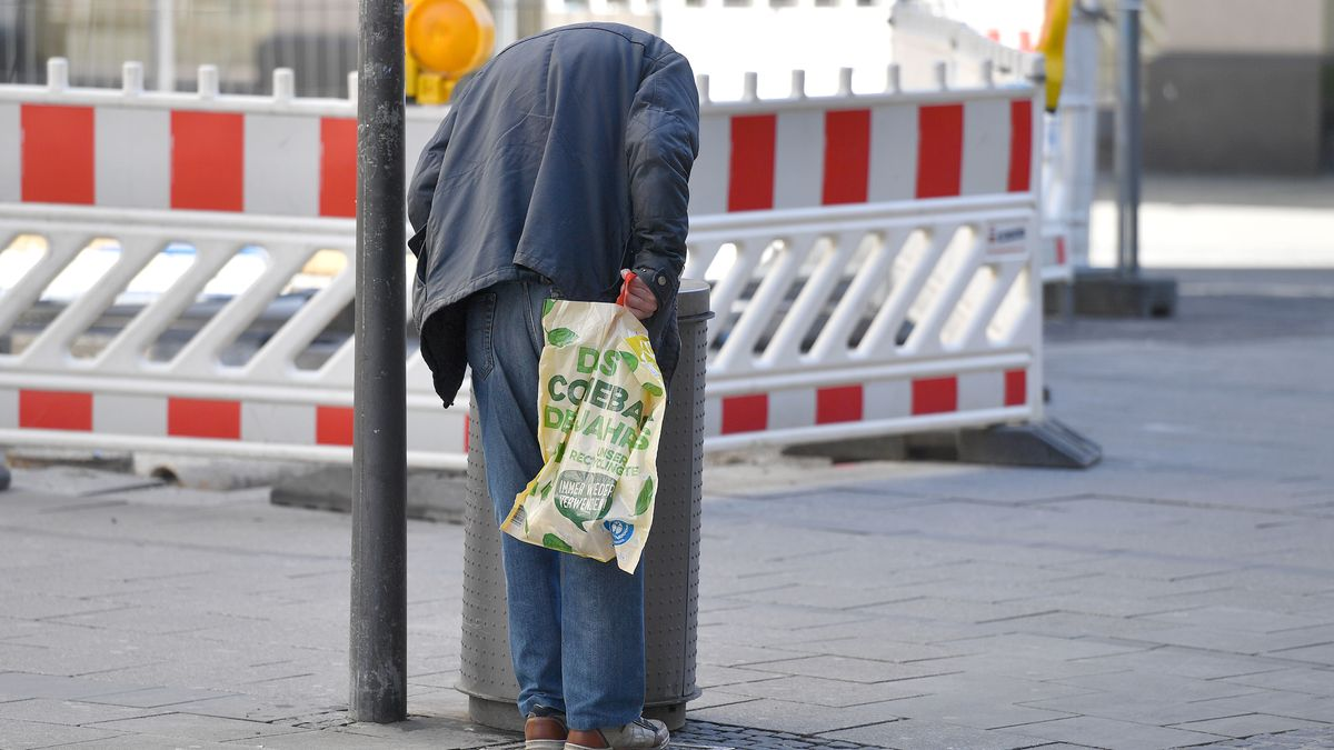 Älterer Mann sucht nach Pfandflaschen in Abfalleimer in Münchner Fußgängerzone