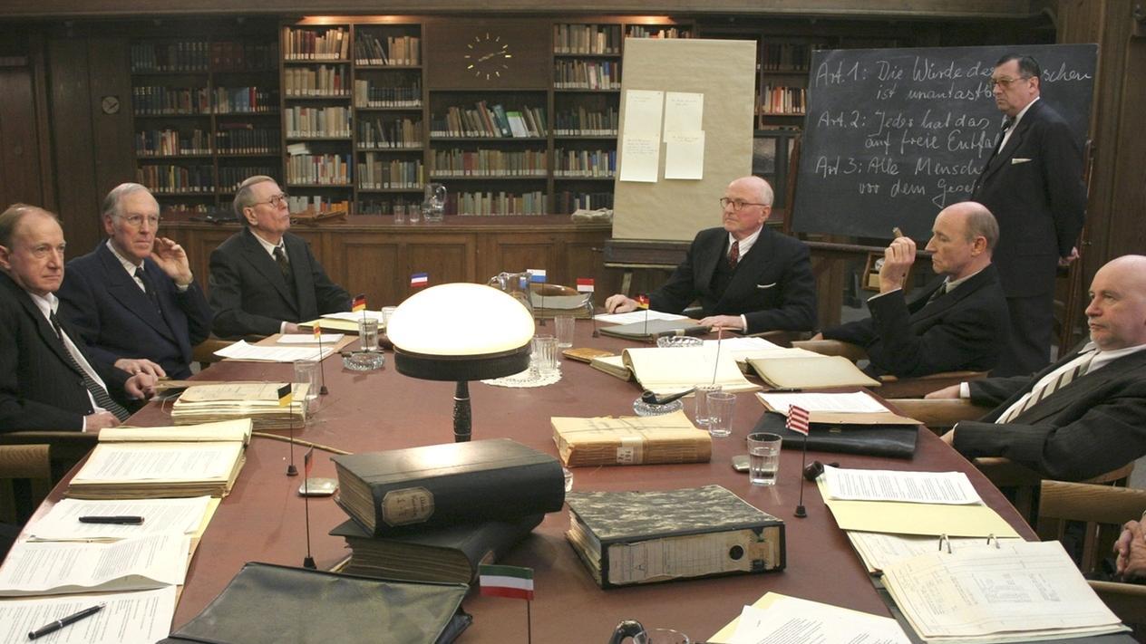 Filmszene des Verfassungskonvents: Ältere Herren im Anzug sitzen um einen ovalen Tisch
