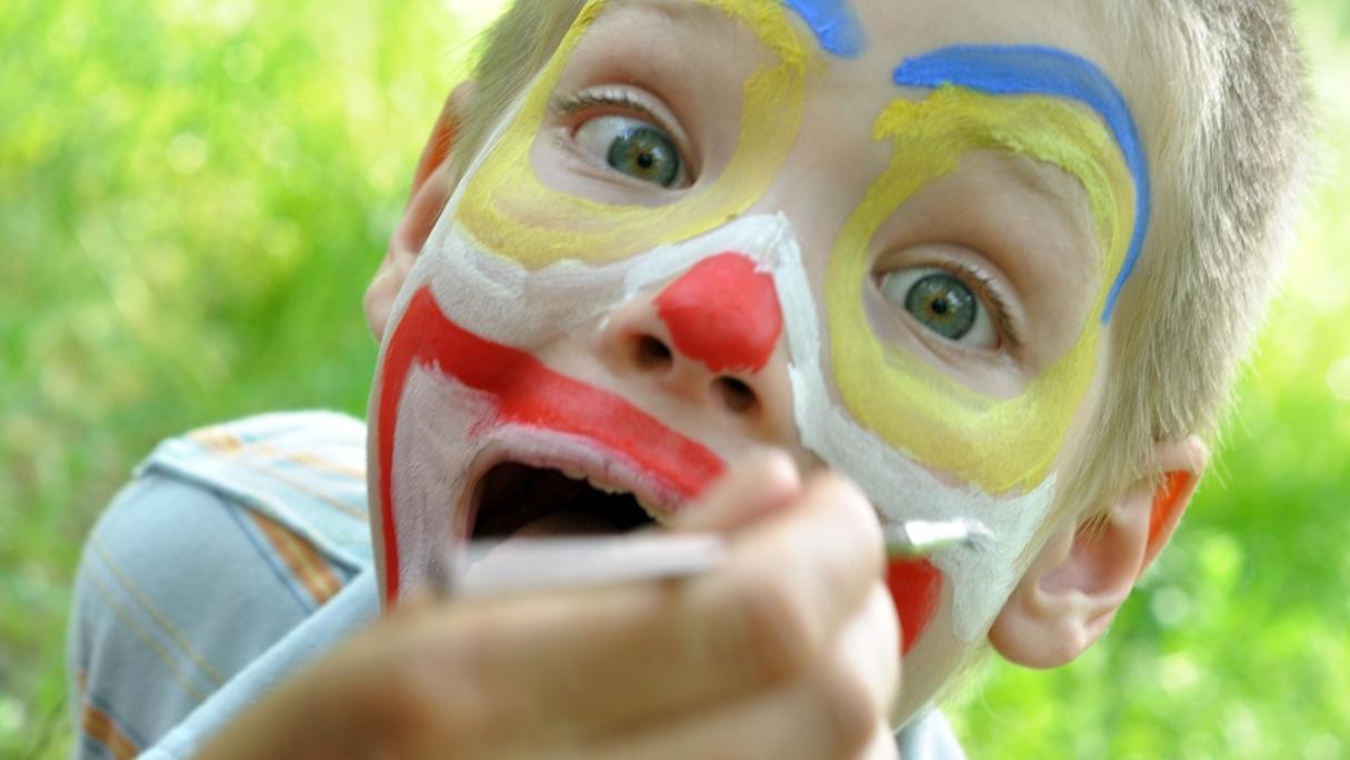 Kind wird als Clown geschminkt.