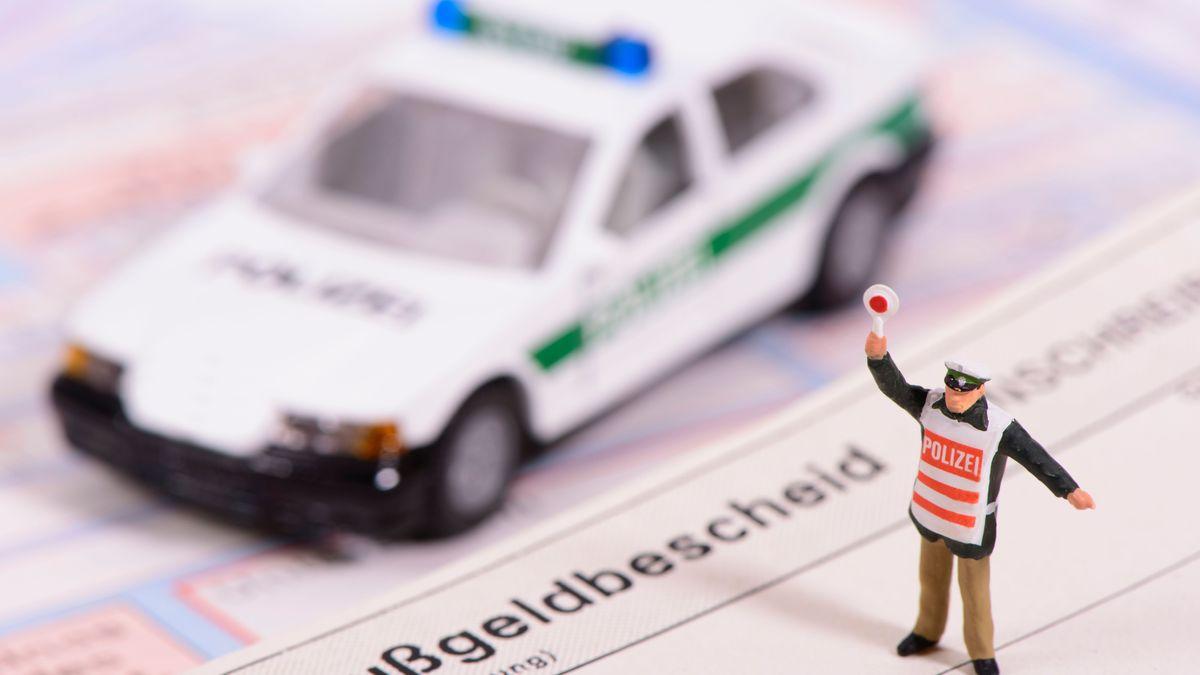 Spielzeugpolizeiauto und Polizeifigürchen auf einem Bußgeldebescheid