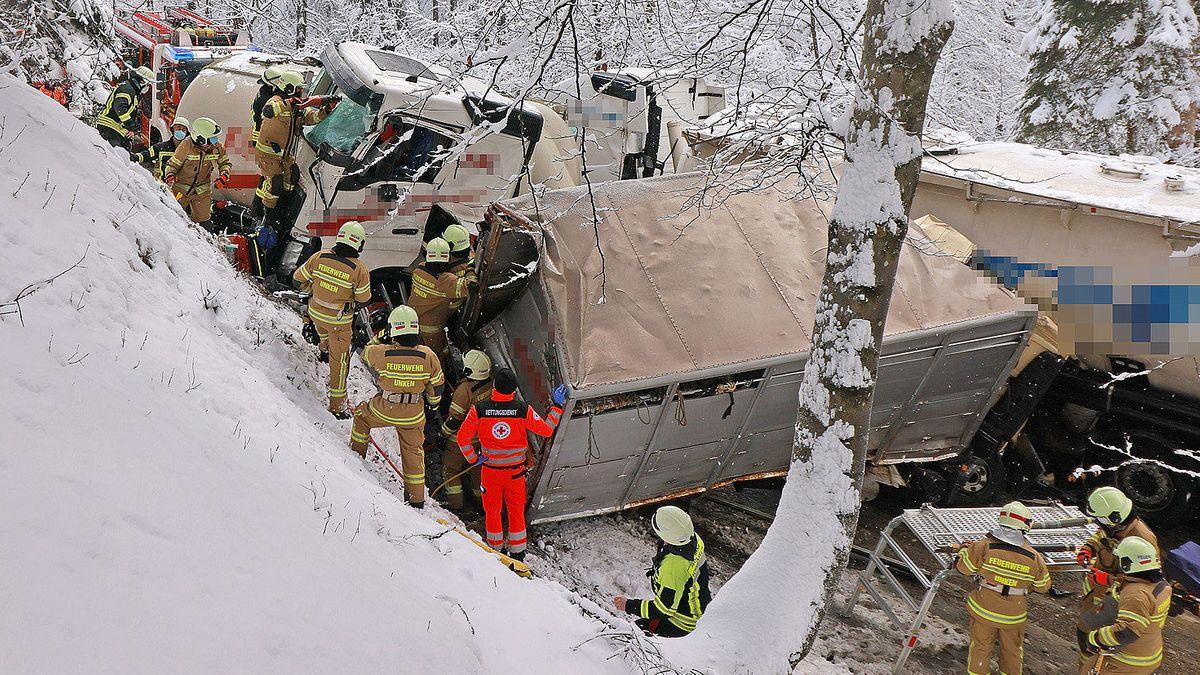 Rettungskräfte bergen die stark beschädigten Lkw.