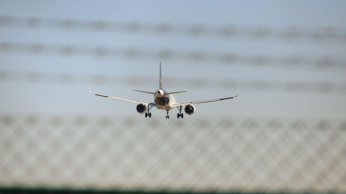 """""""Abschiebeflug"""": Eine landende Lufthansa-Maschine hinter einem Zaun und Stacheldraht (Symbolbild)."""