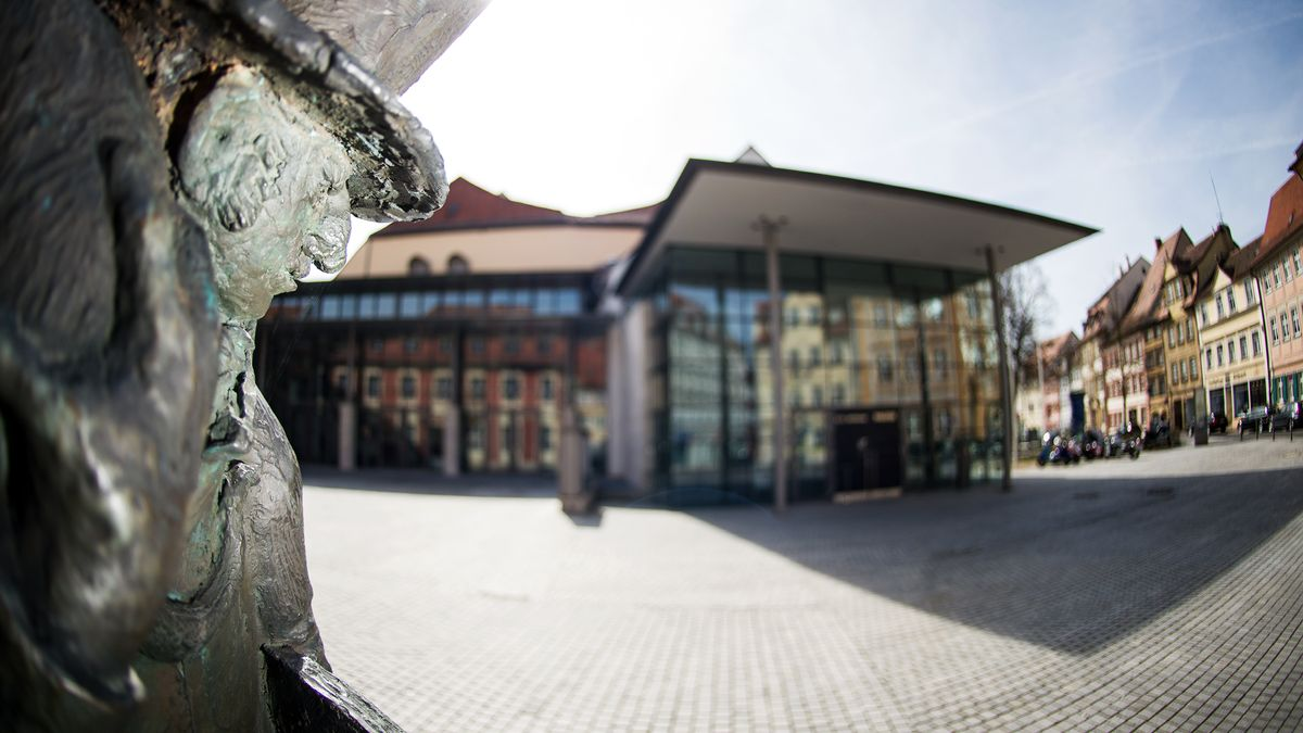 Ein Denkmal, das den Dichter Ernst Theodor Amadeus Hoffmann zeigt, steht auf dem nach ihm benannten Platz in Bamberg. Im Hintergrund ist das E.T.A.-Hoffmann-Theater zu sehen.