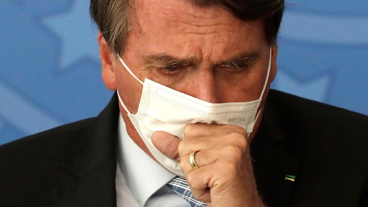 Brasiliens Präsident Jair Bolsonaro hustet am 10. März 2021 in seinen Mund-Nasen-Schutz.