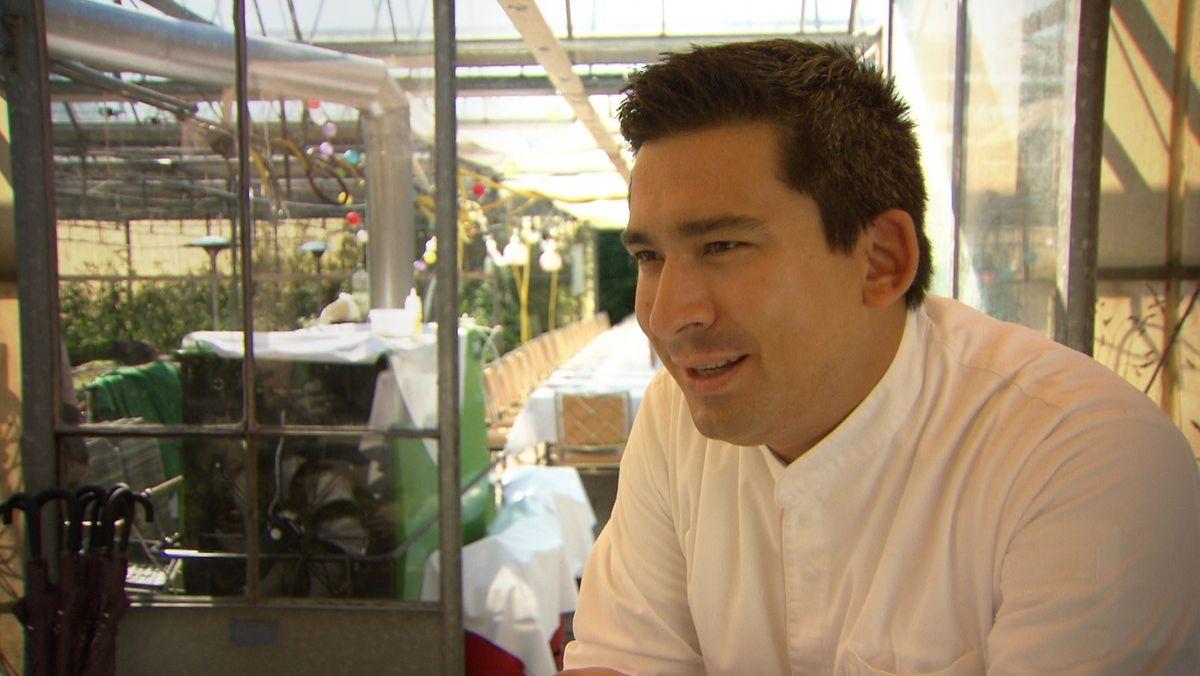 Junger Mann in Kochkleidung mit langer Tafel im Hintergrund