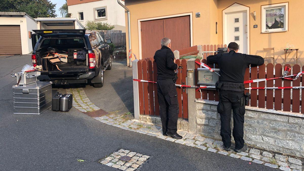 Zwei Polizisten stehen vor einem Haus, das mit Polizeiband abgesperrt ist.